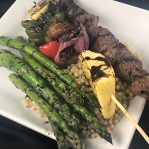 Prime Black Angus steak kabobs with red and green peppers, onions, & mushrooms. Served over a bed of Mediterranean couscous with grilled asparagus.